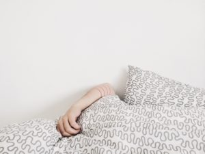 Arm emerging from quilt and pillow